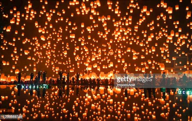 thousands of floating fire paper lanterns in the night sky with reflection in the pool at yee peng festival. loy krathong celebration at sansai, maejo university, chiangmai, thailand - traditional festival stock pictures, royalty-free photos & images