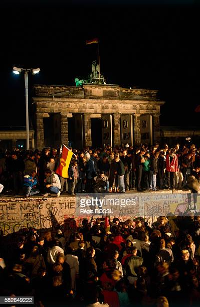 Thousands of Germans gather to celebrate the demise of Communism with the symbolic fall of the Berlin Wall