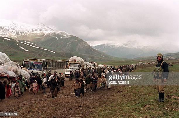 Thousands of Iraqi Kurdish refugees cross the IraqIran border at Hadji Omran point near Piranshar 12 April 1991 while an Iranian soldier looks on...