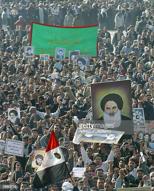 Thousands of Iraqi Shiite Muslims waving an Iraqi flag and pictures of leading Shiite cleric Grand Ayatollah Ali al-Sistani and other revered figures...
