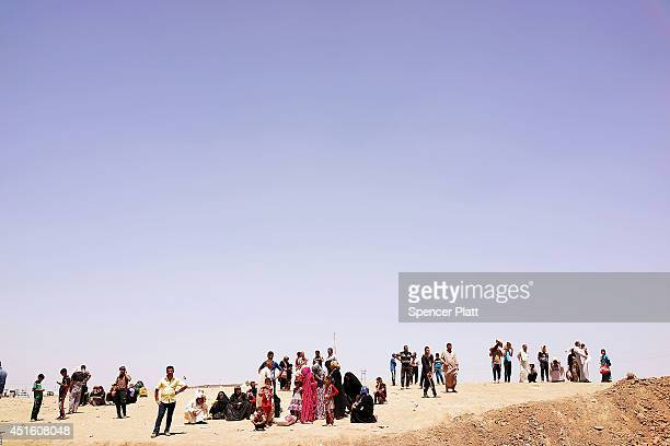 Thousands of Iraqis who have fled recent fighting in the cities of Mosul and Tal Afar try to enter a temporary displacement camp but are blocked by...