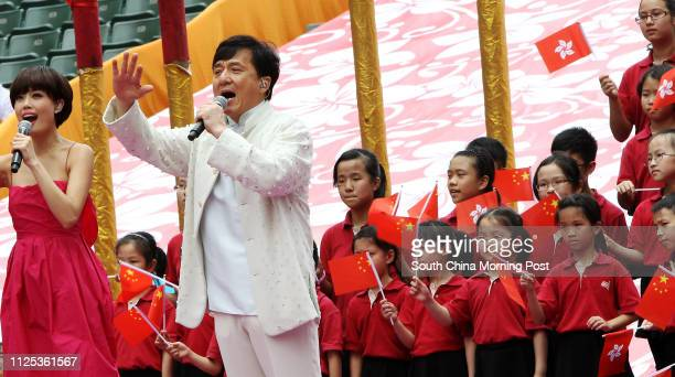 Thousands of jubilant people waving Hong Kong and Chinese flags endured hot summer weather to watch performances by local singers and members of the...