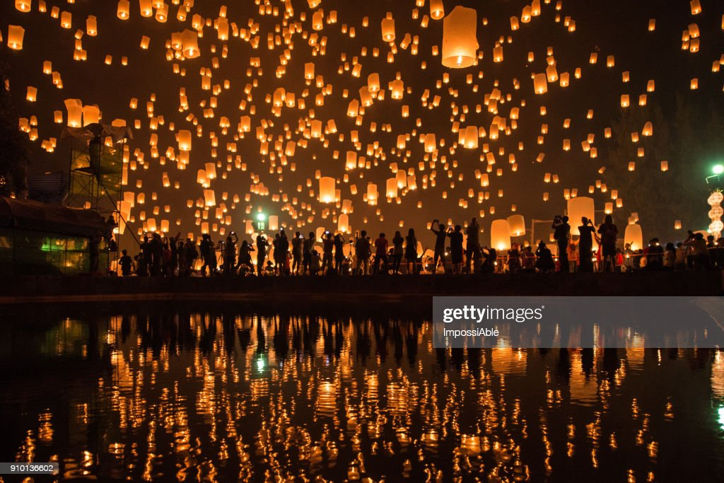 Thousands of Lanterns in the sky with the reflection on the water with people watching.Yeepeng festival, Chiangmai, Thailand : Stock Photo