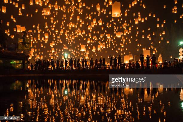 thousands of lanterns in the sky with the reflection on the water with people watching.yeepeng festival, chiangmai, thailand - image stock pictures, royalty-free photos & images