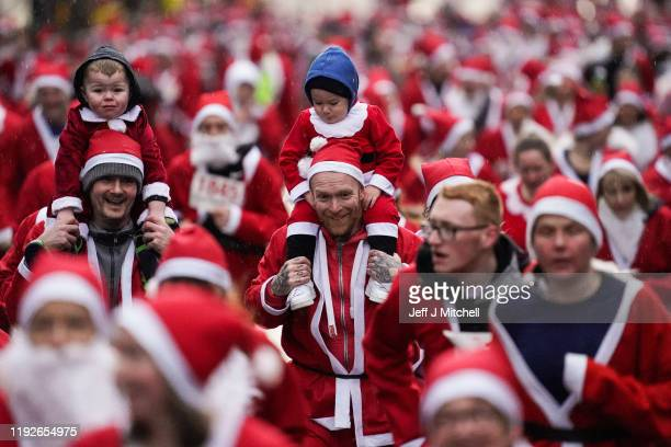 Thousands of members of the public dressed in Santa suits make their way through the streets December 8 2019 in Glasgow The annual 5k fun run will...
