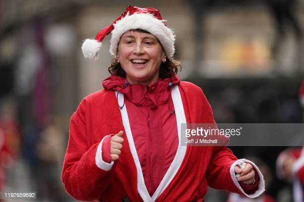 Thousands of members of the public dressed in Santa suits make their way through the streets on December 8 2019 in Glasgow The annual 5k fun run will...