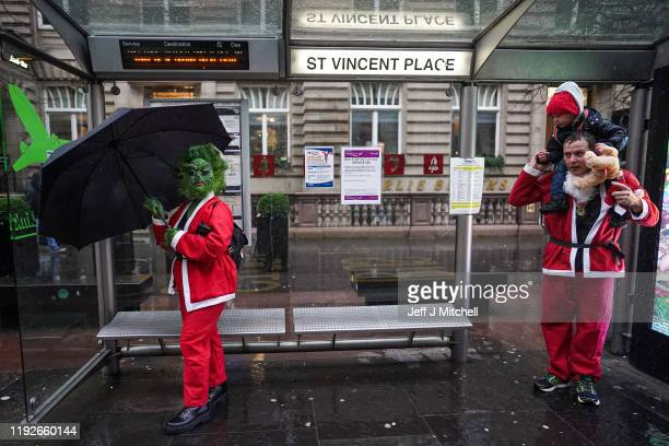 Thousands of members of the public dressed in Santa suits make their way through the streets during the Santa dash on December 8 2019 in Glasgow The...