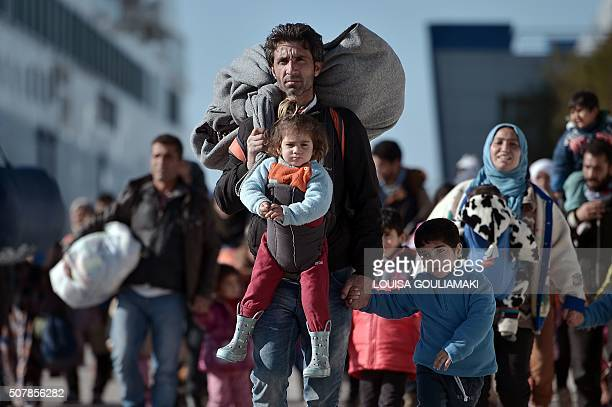 TOPSHOT Thousands of migrants and refugees walk through the port of Piraeus after arriving from the Greek islands of Lesbos and Chios on February 1...