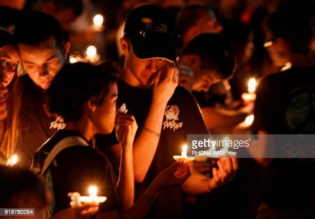 Thousands of mourners hold candles a candlelight vigil for victims of the Marjory Stoneman Douglas High School shooting in Parkland Florida on...