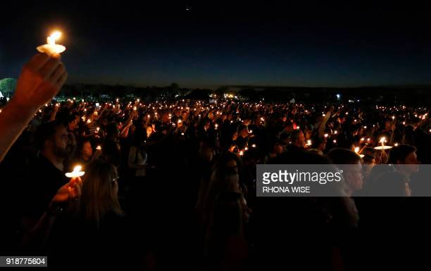 TOPSHOT Thousands of mourners hold candles during a candlelight vigil for the victims of Marjory Stoneman Douglas High School shooting in Parkland...