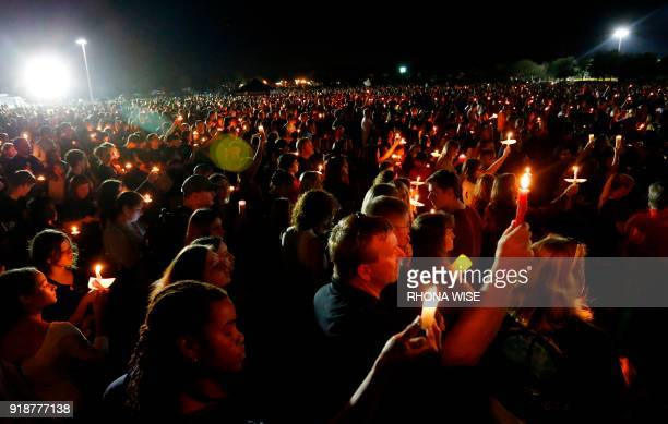 Thousands of mourners hold candles during a candlelight vigil for the victims of Marjory Stoneman Douglas High School shooting in Parkland Florida on...