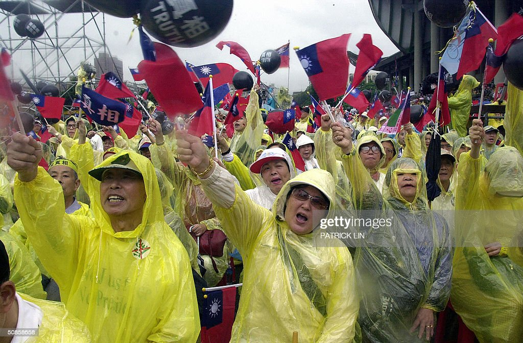 Thousands of opposition supporters clad in raincoats, wave Taiwanese national flag during a protest rally in Taipei, 20 May 2004 as President Chen is sworn in for a second four-year term. The opposition is disputing Chen's re-election claiming it was the result of unfair election. Chen won the 20 March presidential polls by a razor-thin margin of 0.22 percent, or 30,000 votes.