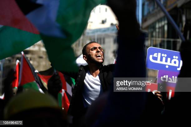 TOPSHOT Thousands of Palestinians waving national flags take part in a protest against a social security law proposed by the Paleslitnian Authority...
