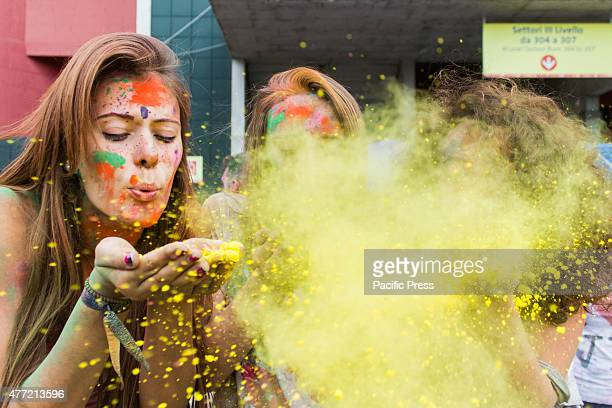 Thousands of people at the second edition of the Turin Holi Fusion, the Festival of Colors of Indian origin. Girls blowing on yellow color.