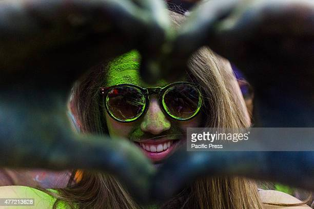 Thousands of people at the second edition of the Turin Holi Fusion, the Festival of Colors of Indian origin. A girl makes a heart with her hands.