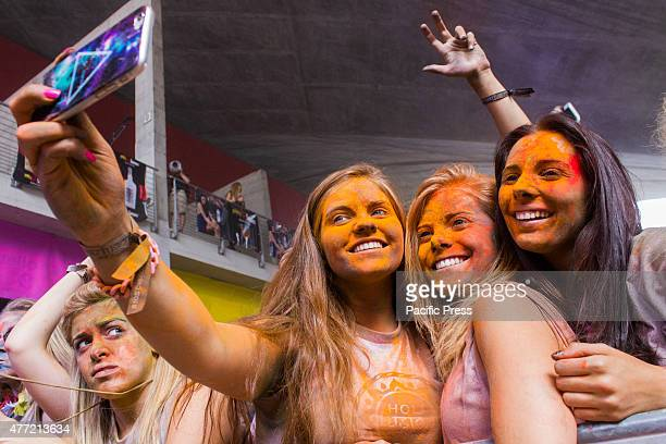 Thousands of people at the second edition of the Turin Holi Fusion, the Festival of Colors of Indian origin. Some girls take a selfie.