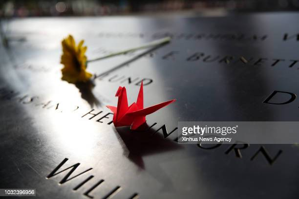 A flower and a paper crane are placed on a plate on which the names of 9/11 victims were inscribed around the South Pool at the National September 11...