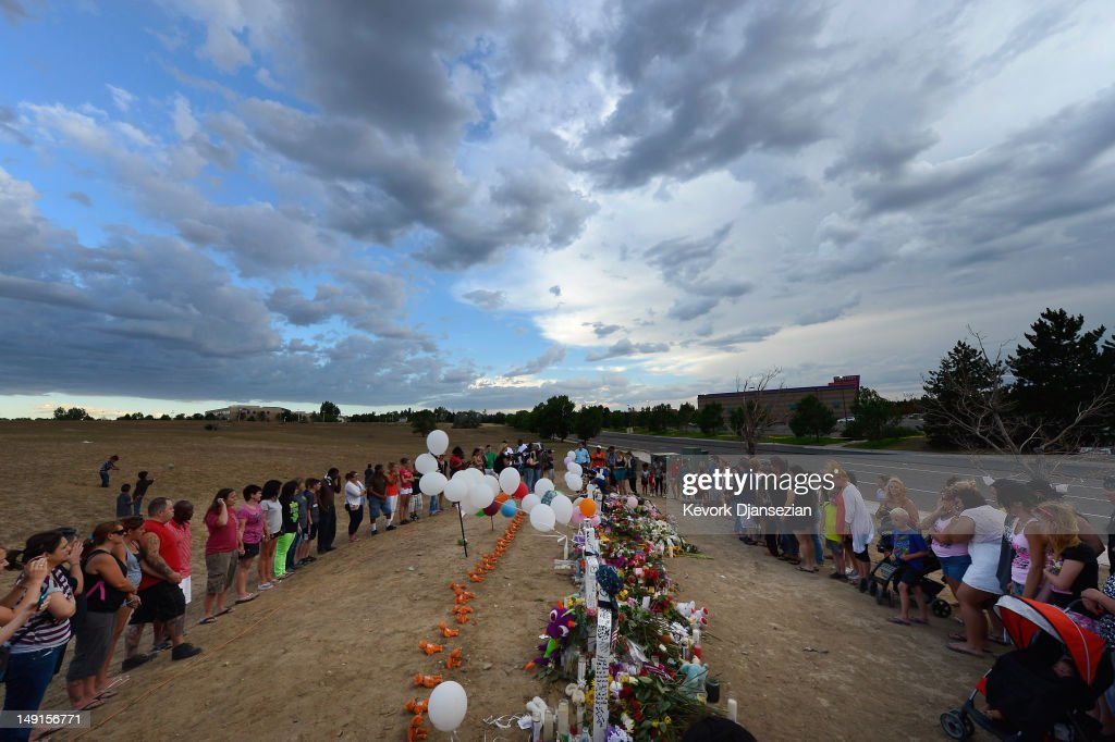 Thousands of people continue to visit the makeshift memorial for the 12 movie theater shooting victims built across the street from the Century 16 theater July 23, 2012 in Aurora, Colorado. Suspect James Holmes, 24, allegedly went on a shooting spree and killed 12 people and injured 58 during an early morning screening of 'The Dark Knight Rises.'