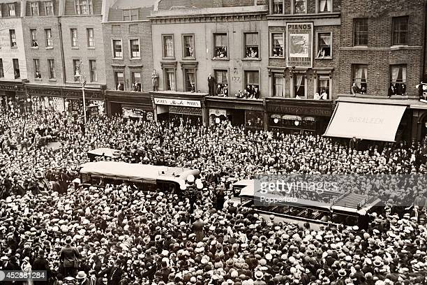 Thousands of people crowd the streets of Islington to congratulate the Arsenal football team winners of the FA Cup as they parade the Cup in...