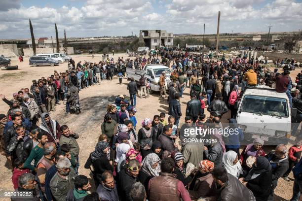 Thousands of people displaced from Afrin line up to receive bread in the village of Fafin South of Tall Rafat An estimated 400000 refugees fleeing...