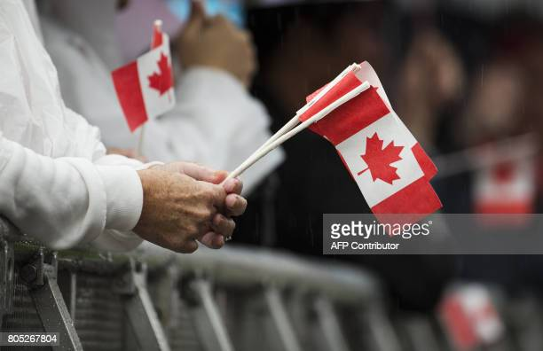 Thousands of people gather in the heavy rain to celebrate Canada's 150th birthday on Parliament Hill in Ottawa on July 1 2017 Britain's Prince...
