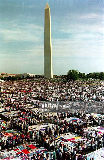 Thousands of people gather to view the AIDS Memorial Quilt on display on the Washington Monument grounds 10 October 1992 in Washington DC The Quilt...