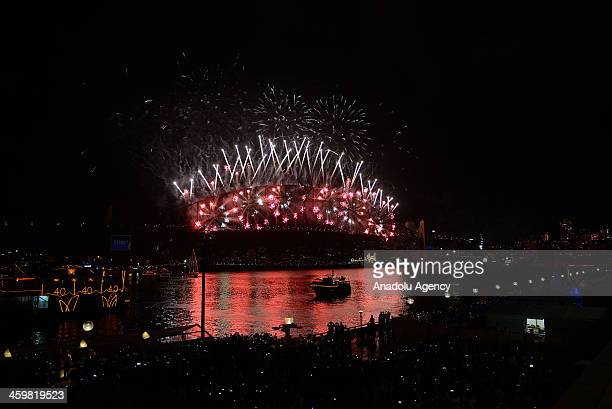 Thousands of people gather to watch New Year's Eve fireworks show over Sydney's iconic Harbour Bridge on January 1 2014