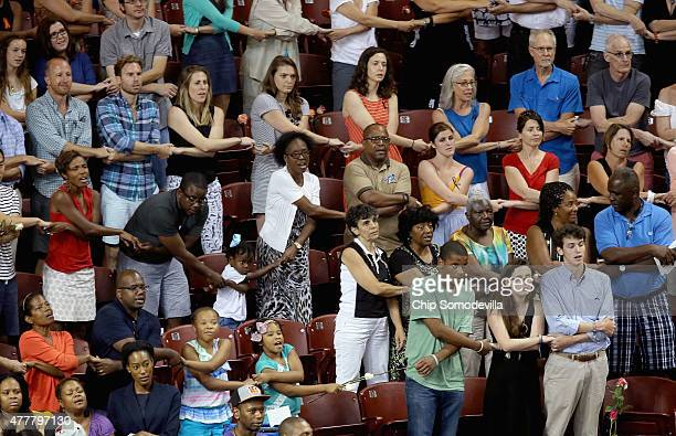 """Thousands of people hold hands and sing """"We Shall Overcome"""" during a prayer vigil for the nine victims of the Emanuel AME Church shooting at the..."""