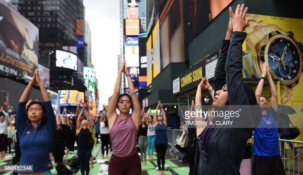 TOPSHOT Thousands of people participate in 'Mind Over Madness Yoga' an annual allday outdoor yoga event during the summer solstice in Times Square on...