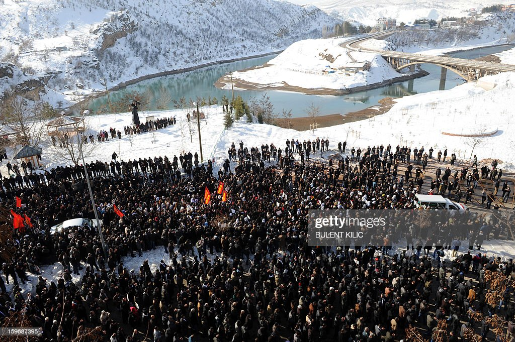 Thousands of people pay their respect around the coffin of Kurdish activist Sakine Cansiz, shot dead in the French capital, during the funeral on January 18, 2013 in Tunceli, her hometown in the Kurdish majority southeast of Turkey. People gathered inTunceli, to pay a final tribute to Sakine Cansiz who was assassinated in Paris last week. The growing crowd of participants, men and women adorned in white scarves, a symbol of peace, marched in a funeral many in Turkey feared would turn into a violent protest. The three women, one of them Sakine Cansiz, a co-founder of the outlawed Kurdistan Workers' Party (PKK), were found fatally shot, at least three times in their heads, at a Kurdish centre in Paris last week. French police were hunting the unknown assailants.