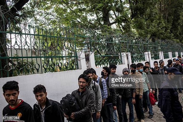 Thousands of people queue on the street outside a government building as they wait for free bus rides out of the city center on on April 29, 2015 in...