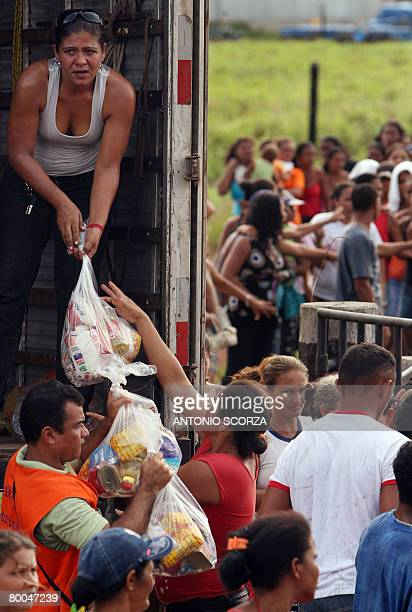 Thousands of people receive a basket of basic food at the entrance of the farm of Tailandia's mayor on February 28 2008 in the northern Brazilian...
