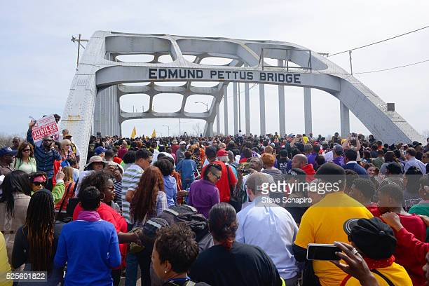 Thousands of people reenact the historic marches to Selma by walking over the Edmund Pettus Bridge during the Selma 50th anniversary celebrations.