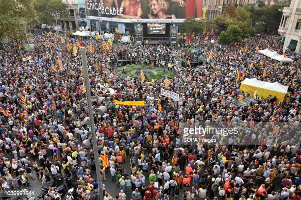 Thousands of people seen gathering at the Economy headquarters during protests in support of Catalonia's independence and commemorate the first...