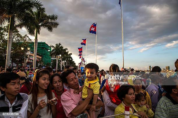 Thousands of people stand waiting to greet the King of Cambodia Norodom Sihamoni on the riverside during the first day of the Water Festival on...