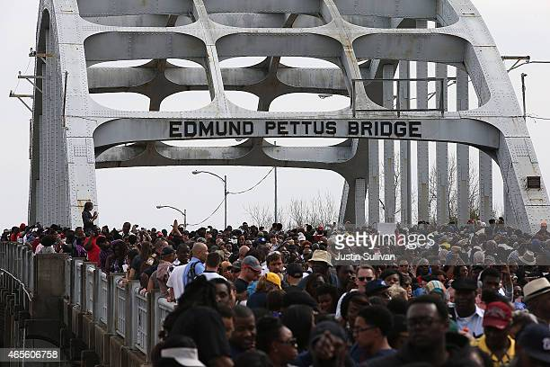 Thousands of people walk across the Edmund Pettus Bridge during the 50th anniversary commemoration of the Selma to Montgomery civil rights march on...