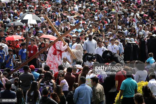 Thousands of people watch as Henry Colindres portrays Jesus during a traditional Via Crucis or Way of the Cross procession that temporarily halted...