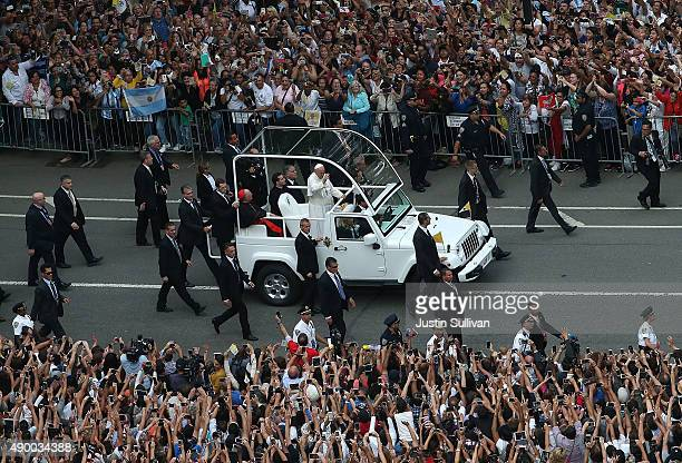 Thousands of people watch Pope Francis ride in the popemobile through Central Park on September 25, 2015 in New York City. The pope is in New York on...