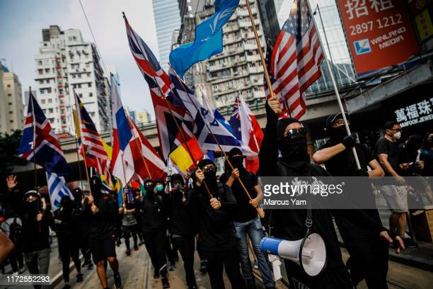 Thousands of prodemocracy demonstrators with international flags march in defiance of the upcoming China's national day in Wan Chai area of Hong Kong...