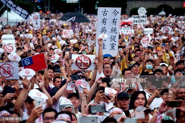 """Thousands of protesters hold placards with messages """"reject red media and safe guard the nation's democracy"""" during a rally on Ketagalan Boulevard in..."""