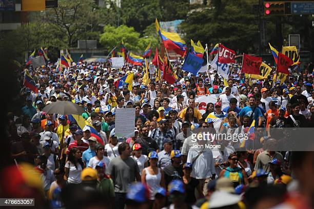 Thousands of protesters march in an antigovernment demonstration on March 4 2014 in Caracas Venezuela Meanwhile workers made last minute preparations...
