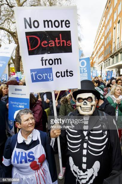 Thousands of protesters march towards Parliament Square as they hold placards during a demonstration in support of the National Health Service on...