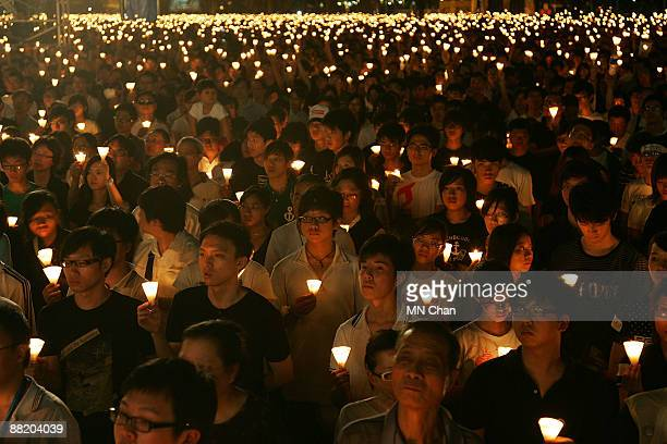 Thousands of protestors hold candles during a candlelight vigil for the 20th anniversary of June 4 Tiananmen Square Massacre in Beijing at Victoria...