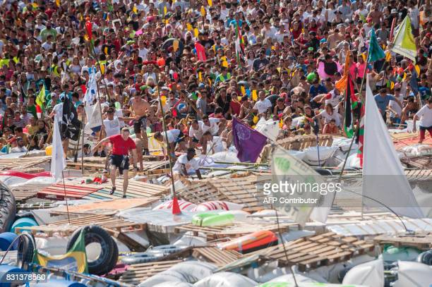 Thousands of revellers run to board their hand-made rafts floating in the port of the northen Spanish Basque city of San Sebastian during the...