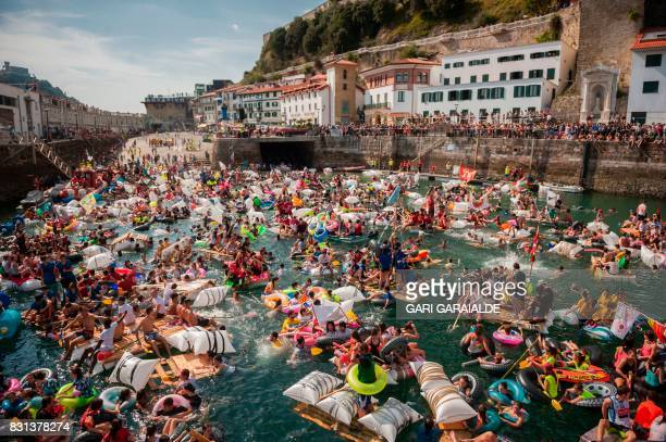 "Thousands of revellers try to navigate their hand-made rafts in the port of the northen Spanish Basque city of San Sebastian during the ""Abordaje""..."