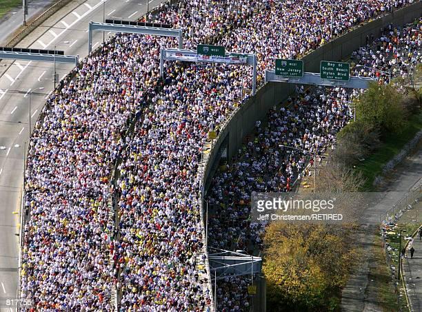 Thousands of runners cross the Verrazano-Narrows bridge at the start of the New York City Marathon November 7, 1999. Over 30,000 men and women run in...