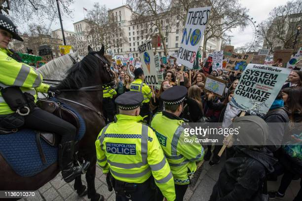 Thousands of school children protesting about Climate Change gather outside Downing Street and are moved back by police and mounted police on March...