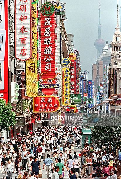 Thousands of shoppers walk along the pedestrian mall of Nanjing road, the main shopping street in Shanghai, 21 September 1999. City authorities...
