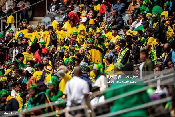 Thousands of South African ruling Party African National Congress supporters and mourners sing and dance during a memorial service for the late South...