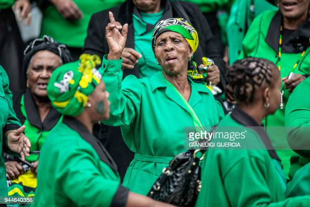 Thousands of South African ruling Party African National Congress supporters and mourners sing and dance during a memorial service for late South...
